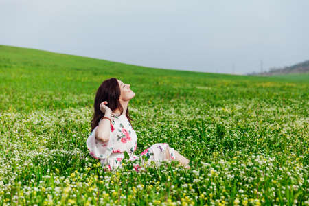 Beautiful brunette woman in dress with flowers sits in spring field
