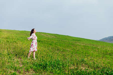 Beautiful brunette woman in a dress with flowers stands on the mountain one