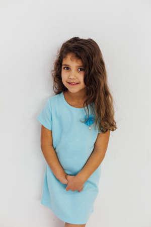 Beautiful little curly girl in a blue dress