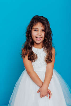 Beautiful little curly girl in a white dress