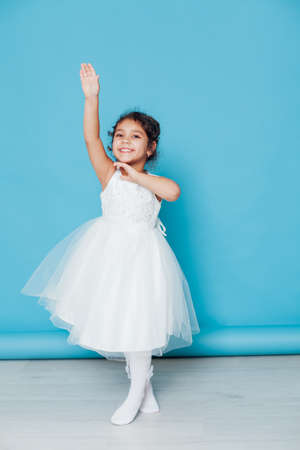 Beautiful little girl dances to the song in a white dress Banque d'images