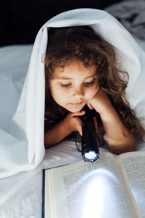 Little girl reads a book with a flashlight in bed