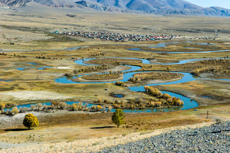 Top view of the Altay Russian village of Ortolyk, the steppe and Altai mountains, the winding Chuya river, Siberia, Russia.