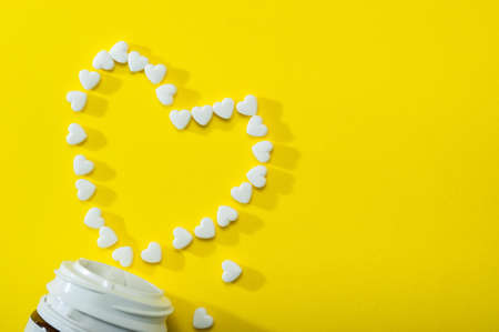 Heart-shaped pills fell out of the bottle on a yellow background. Flat bed, top view.