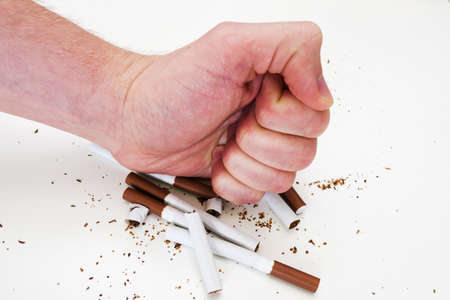 A mans hand destroys, crumples cigarettes on a white background, the concept of Smoking cessation. Imagens