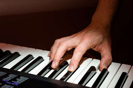 The musician plays the keyboard of the synthesizer with the keys of the piano. At a concert with floodlights.