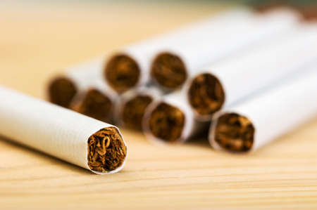 Close-up of a pile of cigarettes and one cigarette on a wooden table. Dangers of smoking.