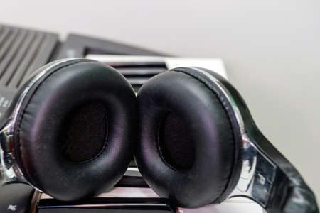 Stylish black headphones lie on the keys of the synthesizer.