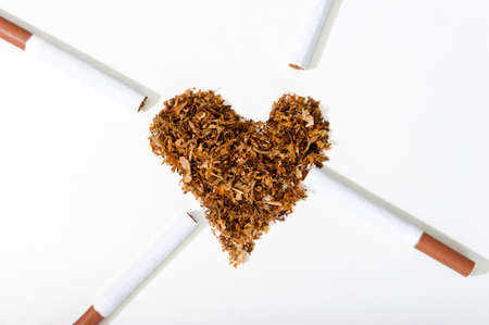 A heart made of cigarette tobacco and four cigarettes lie next to it. The concept of world no tobacco day. Give up smoking. Banque d'images