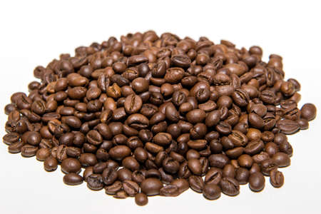 a pile of freshly roasted coffee beans isolated on a white background.