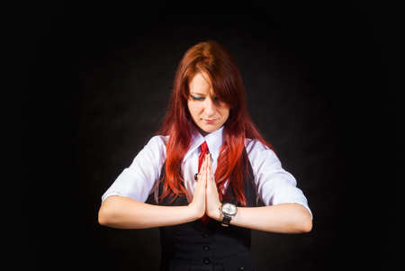 A pleading young redheaded woman a girl in a white blouse a black vest and a red tie on a black background looked down. Holding his hands together in prayer.