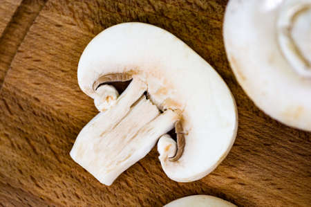 Cut an edible white mushroom on a wooden Board. 免版税图像