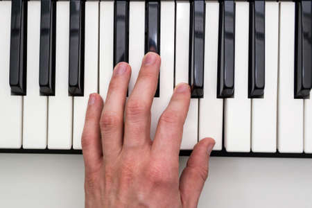 Close-up of the hand of a musical artist playing the piano, a mans hand, classical music, keyboard, synthesizer, pianist.