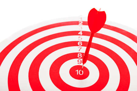 Close-Up of a Bulls Eye On a Wall with a red dart on a white background.