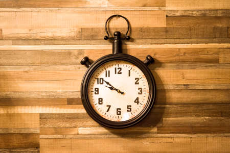 Old authentic clock hanging on a wooden wall.