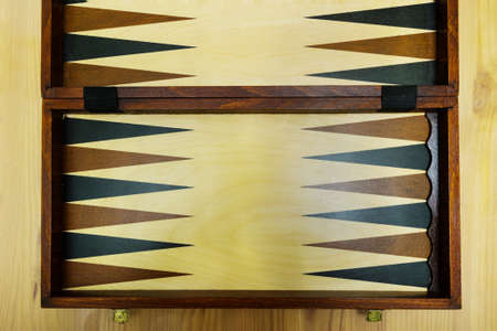 An old wooden backgammon Board on a wooden table.