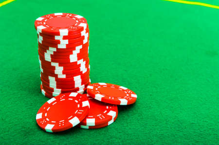 A column of red chips for gambling, poker, on a green background. Casino. Archivio Fotografico