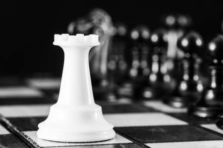 Chess pieces, a white rook on a chessboard, against a row of black pieces. The concept of career, competition, startup. High quality photo