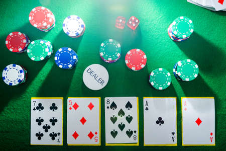 Playing cards and poker chips on top of a green poker table, top view with lighting and sunlight.