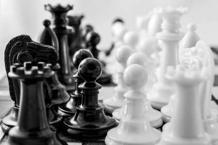A cluster of chess pieces on the Board. Background of the chess table, confrontation, black and white photo