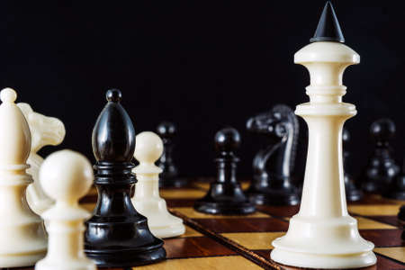 A white king on a chessboard surrounded by several pieces on a black background. Archivio Fotografico