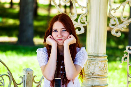 The girl in a white dress leans on a signature stamp of an acoustic guitar