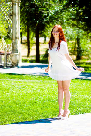 Girl in a white dress curtsy in a city park on a summer day Archivio Fotografico
