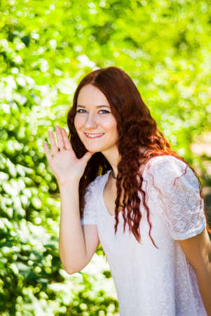 Girl in a white dress waving hand, welcoming or saying goodbye Archivio Fotografico