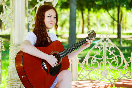 A girl in a white dress with a guitar sits in a park gazebo