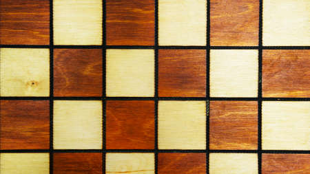 Wooden background of a chessboard close-up. Vintage texture of a chess Board. White and black squares.