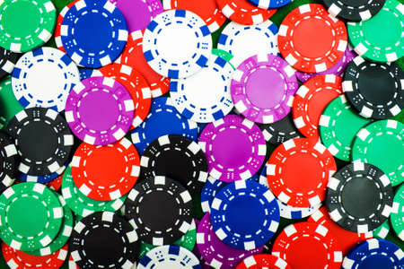 Background of round poker chips is a close-up of different denominations.