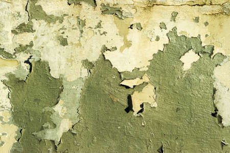An old concrete wall in the color of peeling green paint. Cracked external texture background
