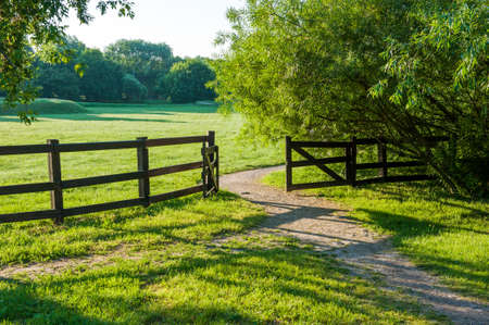 An old wooden cattle gate against the backdrop of a picturesque valley and a meadow with trees in the countryside, on a Sunny summer day.