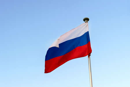 The Russian flag on the flagpole flutters against a blue cloudless sky.
