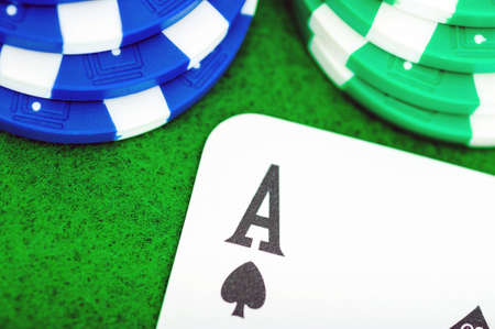 Close-up of the ACE of green and blue poker chips card on the green table. Archivio Fotografico