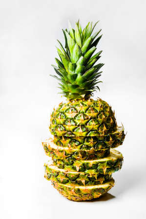 Artistically sliced, standing, delicious pineapple on a white background, isolated, vertical shot. Archivio Fotografico