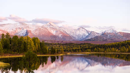 Lake Cicely Altai, Siberia, pink sunset over a lake and mountains in autumn day. Taiga, beautiful sky, mountains with snow peaks. Archivio Fotografico