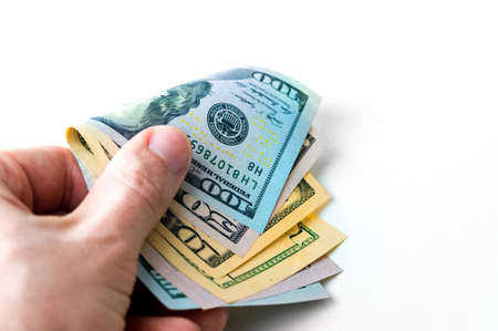 A mans hand with money of more than a hundred dollars isolated on a white background, a bribe, payment.