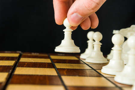 The part of a mans hand that makes the first move in a chess game, raising and moving a pawn one square forward. Dark background.