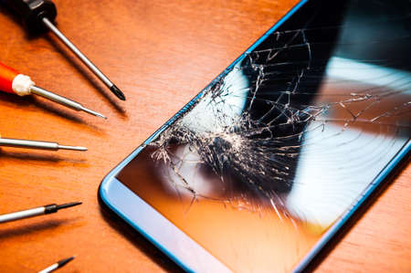 A broken mobile phone with a broken screen with tools, screwdrivers on a wooden table. Electronics repair shops.