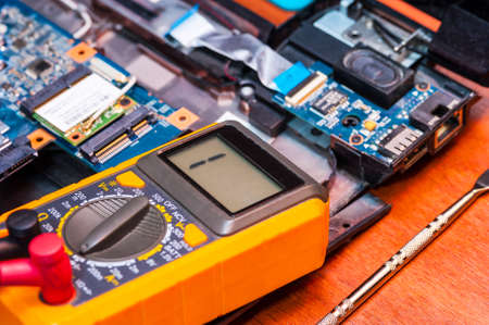 Repair an electronic device using a multimeter by measuring the voltage of the laptop Board using a digital multimeter.