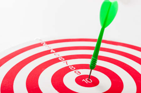 Close-up of a bulls eye with a green dart, hit the target, success. A target with red and white circles.