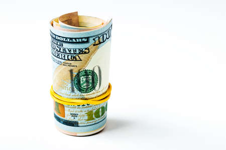 A roll of dollars tied with an elastic band on a white background, one hundred dollars.