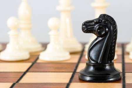 Black knight chess piece close-up and white pawns, on a white background. Chess game, strategy.