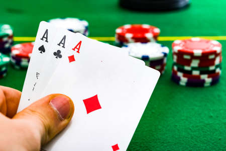 A man shows his three aces during a game of poker, gambling, risk. Archivio Fotografico