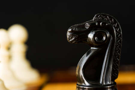 Black knight chess piece close-up and white pawns, on a black background.