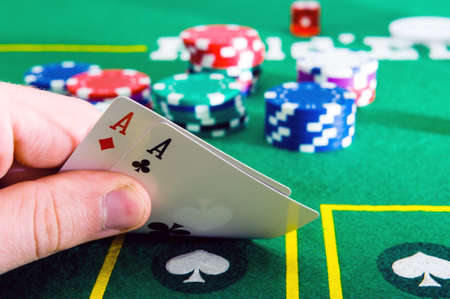 A man shows his deck of aces during a poker game,