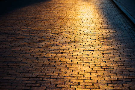 City street covered with paving stones, background, with a bright dawn sun, contour lighting. Archivio Fotografico