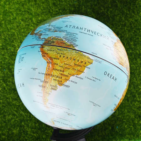 Close-up of South America on a globe with a blurry background, green grass.