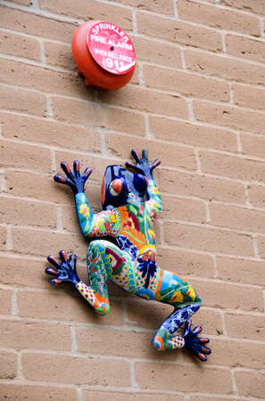 Ceramic gecko on a wall with fire alarm bell photo